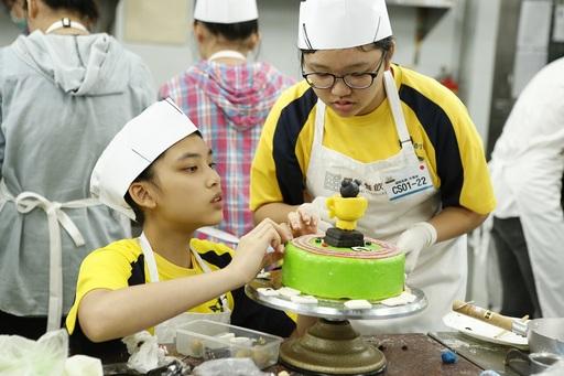 常勝軍武崙國中楊紫姍和趙芷琳展現良好默契,呈現充滿世大運氛圍的蛋糕裝飾,登上校園組王座。