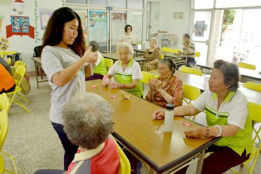 南華大學榮獲教育部青年志工績優團隊「第一名」, 志工隊至社區舉辦「再利用好好玩科學營」,教導長者和學童製作童玩。