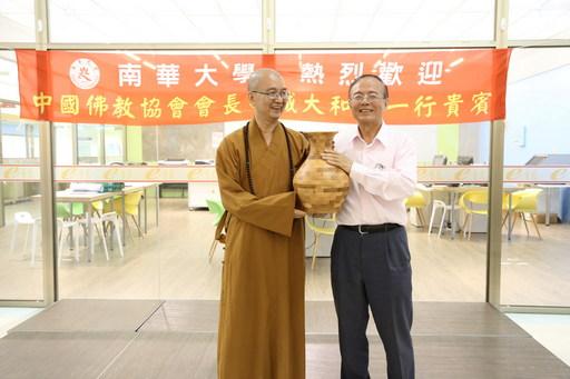中国佛教协会会长学诚大和尚一行莅南华大学参访,林聪明校长(右)致赠创意产品设计学系精心制作的木制拼接花瓶予学诚大和尚(左)。