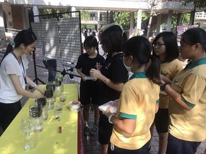 新聞圖說3:師生聚集於展示攤位前,觀察魚菜共生瓶。