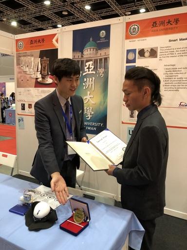 「自動進氣清淨口罩」發明獲得2金2特別獎,韓國代表(左)特地到亞大展位,親自頒獎給江佑均同學,稱讚江的創作。