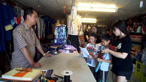 義大「大傳系」學生帶著小學童一起前往周邊店家採訪。(義守大學提供)