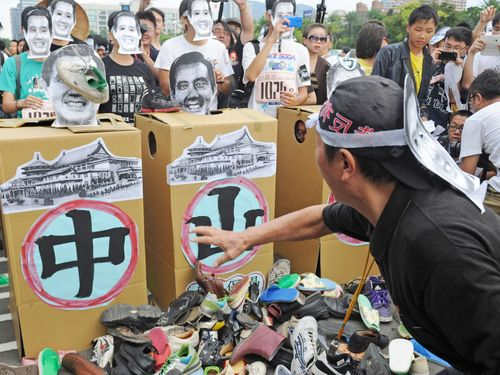 A protester throws shoes at the image of President Ma Ying-jeou in the demonstration held at Sun Yat-sen Memorial Hall.