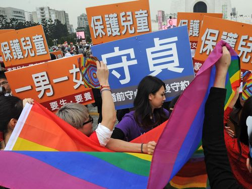 Crowds carrying rainbow flags clash with people holding banners written with slogans, including