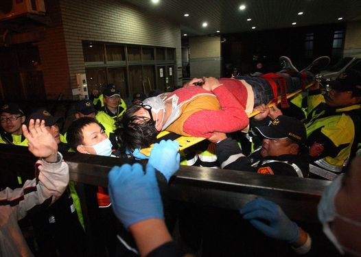 One of the injured is carried away from the Executive Yuan after initial clash Sunday evening.