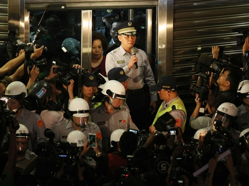 Zhongzheng First Police Precinct chief Fang Yang-ning (left) speaks to the crowd outside the precinct building.