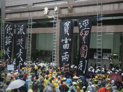 Labor groups gather in front of the Ministry of Labor in Taipei Thursday.