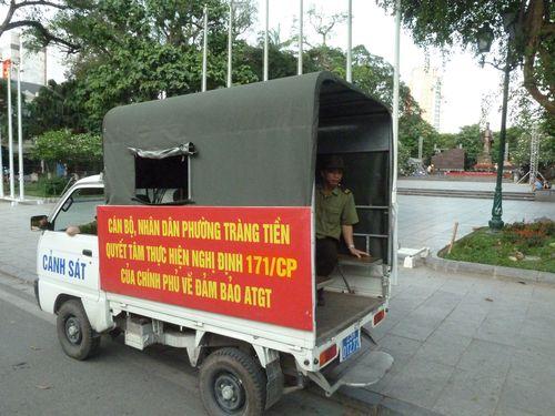 Police vehicle patrols on the street of Hanoi Saturday.