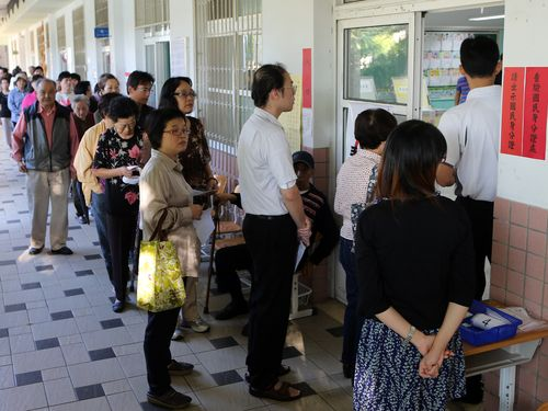 People line up in front of a voting station.