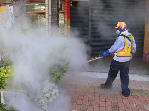 A Kaohsiung city worker spreads pesticide.