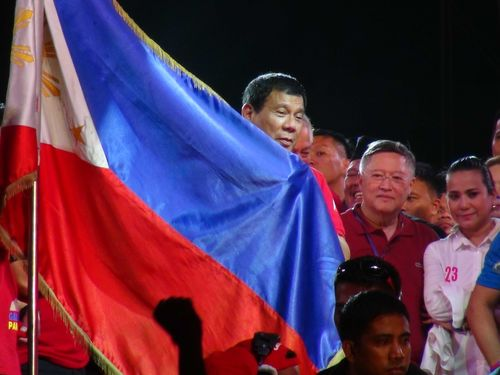 Rodrigo Duterte (center) holds a Philippine flag during his presidential campaign rally May 7.