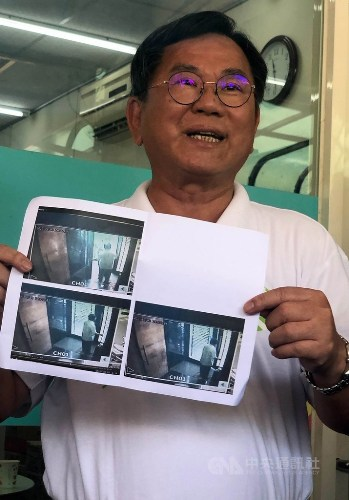 DPP Legislator Chen Ming-wen holds up images from surveillance video in an attempt to prove his innocence