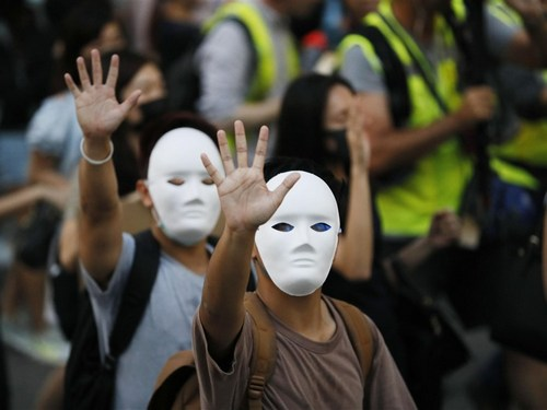 In face masks, Hong Kong people take to the streets Friday to protest the government's decision to ban face masks in an attempt to quell mass demonstrations. (Photo courtesy of  Kyodo News)
