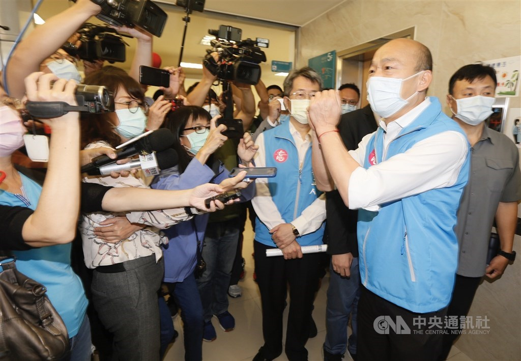Kaohsiung Mayor Han Kuo-yu (front, right) greets reporters when paying a visit to health officials Friday.