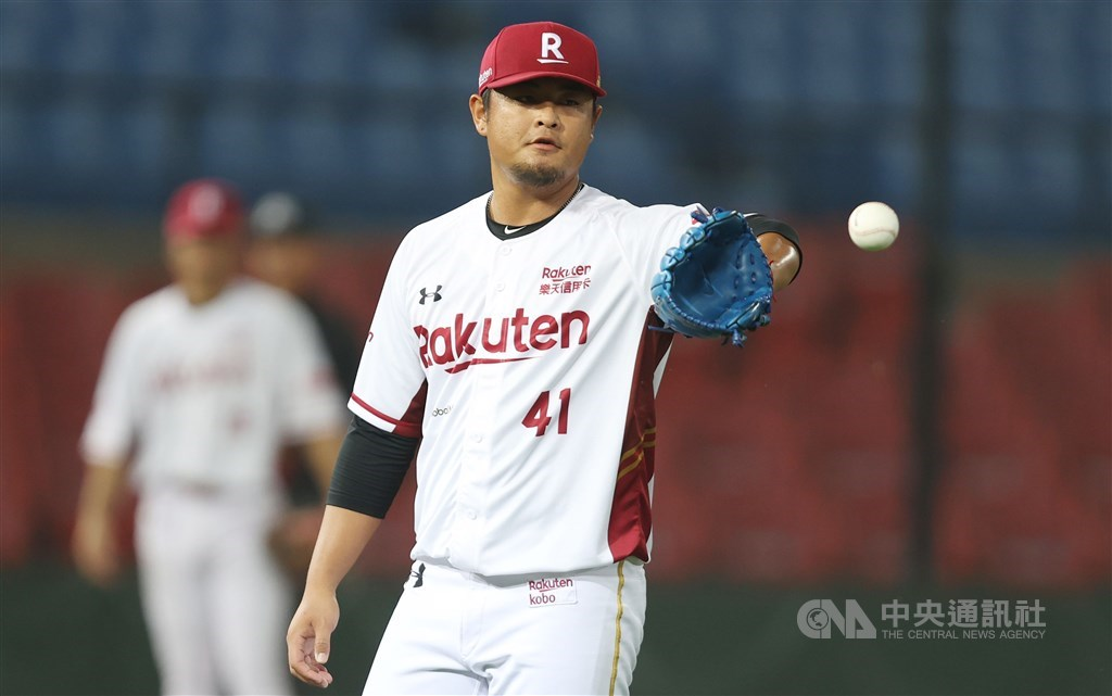 A Rakuten Monkeys player pitches in front of empty stands during a home game May 1.