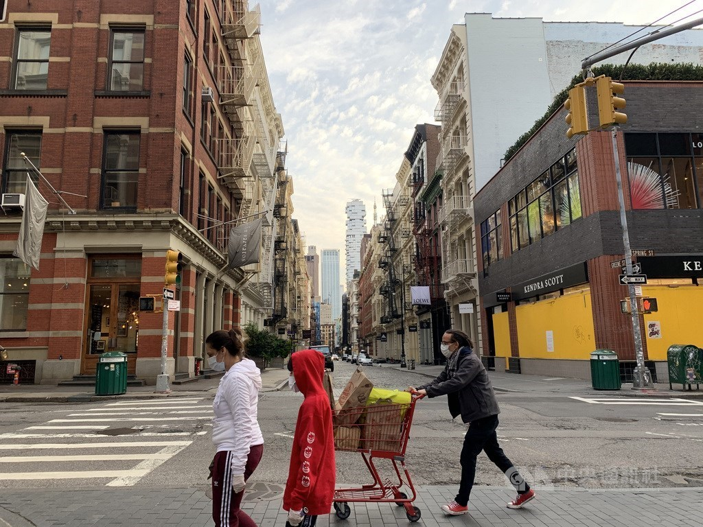 People wear masks while walking on the streets of New York City