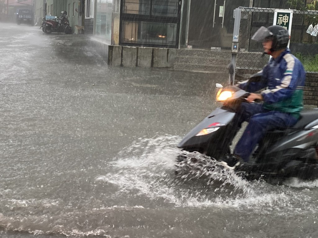 A man rides his scooter through streets flooded by torrential rain in Kaohsiung Friday. (Photo provided by a member of the public)