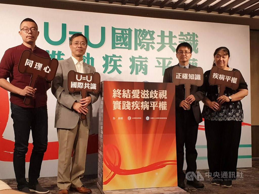 "Hung Chien-ching (second left), head of the Taiwan AIDS Society, holds a signs saying ""Undetectable equals untransmittable,"" while Zhuang Ping (right), who heads the Taiwan AIDS Nurses Association, calls for equality for all patients."