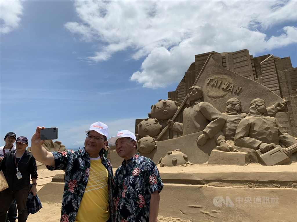 Transportation Minister Lin Chia-lung (in yellow shirt) and Health Minister Chen Shih-chung (right) pose for a selfie in front of the COVID-19 themed sand sculpture. / CNA photo June 29, 2020