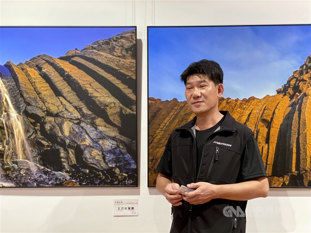 Taiwanese photographer Lee Ming-tsung (李明宗) stands besides his works exhibited at National Dr. Sun Yat-sen Memorial Hall in Taipei