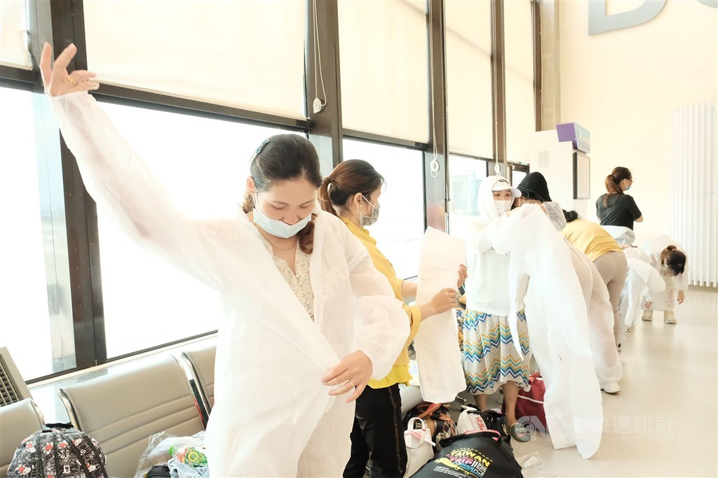 The Vietnamese passengers wear protective gowns before boarding the flight. CNA photo July 7, 2020
