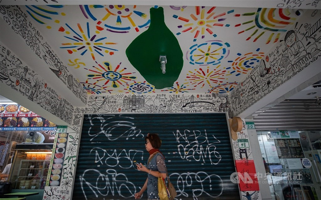 A woman walks past by a closed shop that was put up for rent in early July. CNA file photo