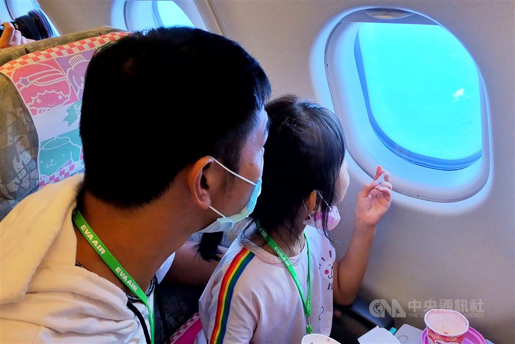 A father and daughter look out of the window during the flight. CNA photo Aug. 8, 2020