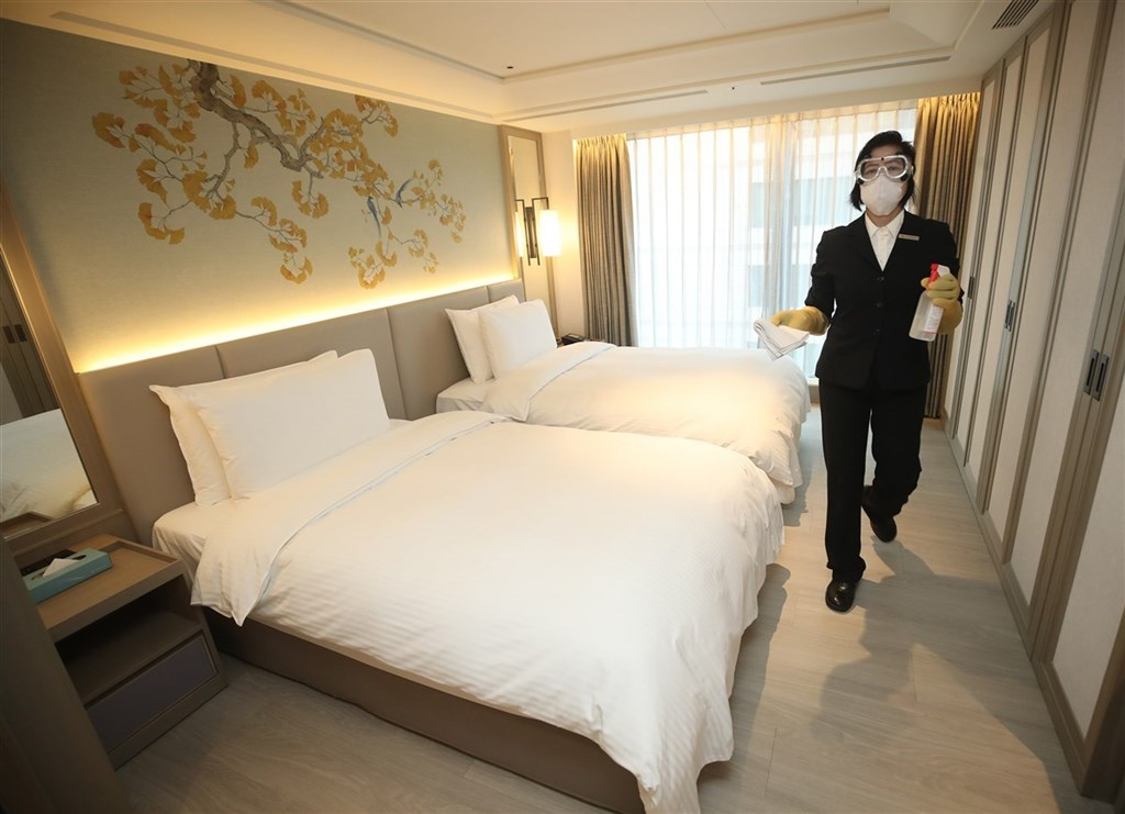An employee at a quarantine hotel disinfects a hotel room/ CNA file photo