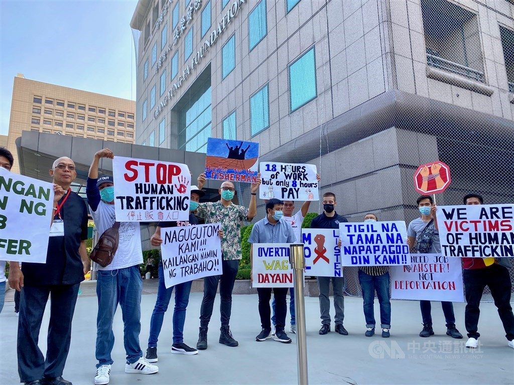 Filipino fishers and their supporters hold up placards to make their plea outside an annual International Workshop on Combating Human Trafficking / CNA photo Sept. 2, 2020