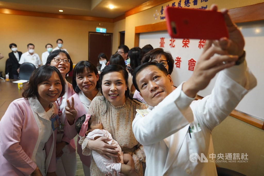 Le Van Dai Trang, carrying her baby daughter, poses for a group selfie with the medical staff at Taipei Veterans General Hospital on Monday / CNA photo Sept. 14, 2020