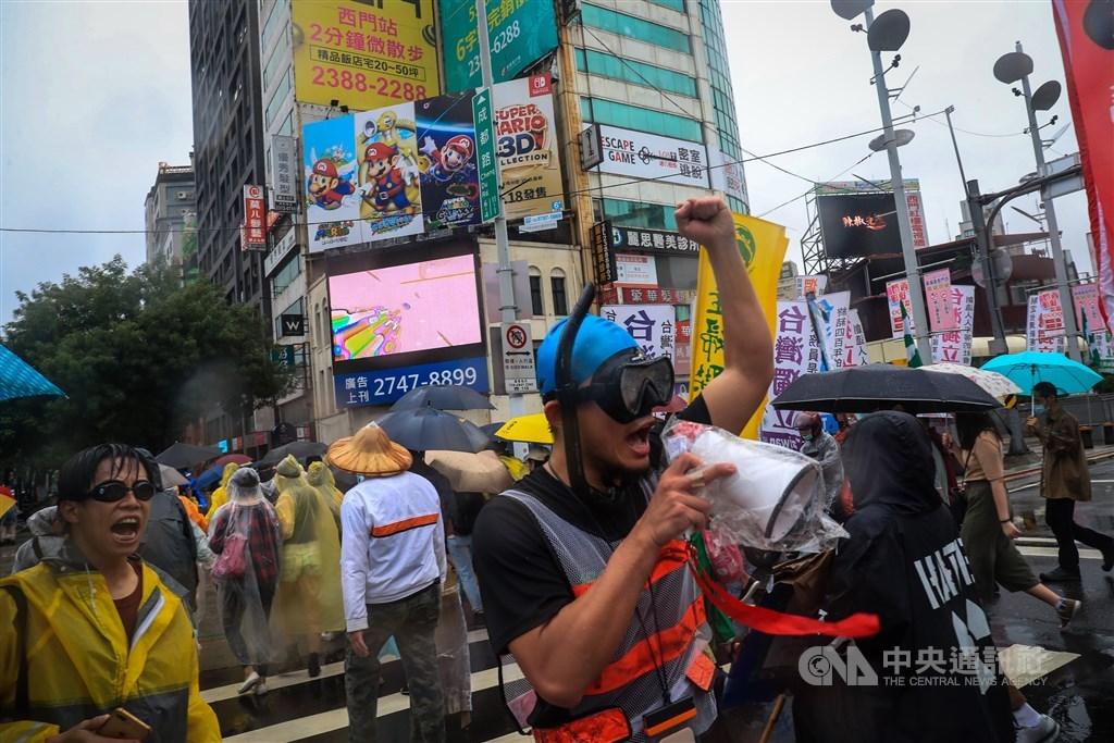 Demonstrators walk past Taipei