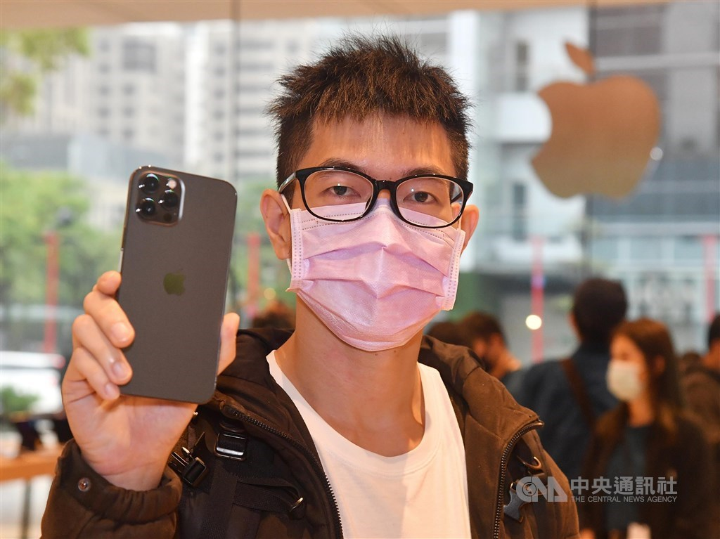 A consumer named Kao shows off his new iPhone 12 purchase at the Apple store in Taipei