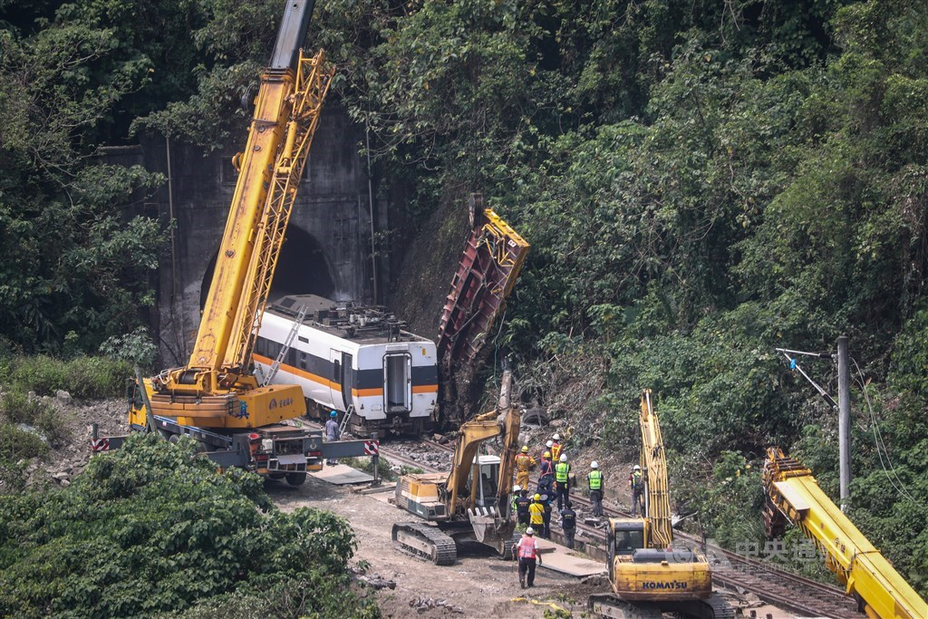The wreckage of the truck is lifted from between the train and the slope by the track Saturday morning. CNA photo April 3, 2021