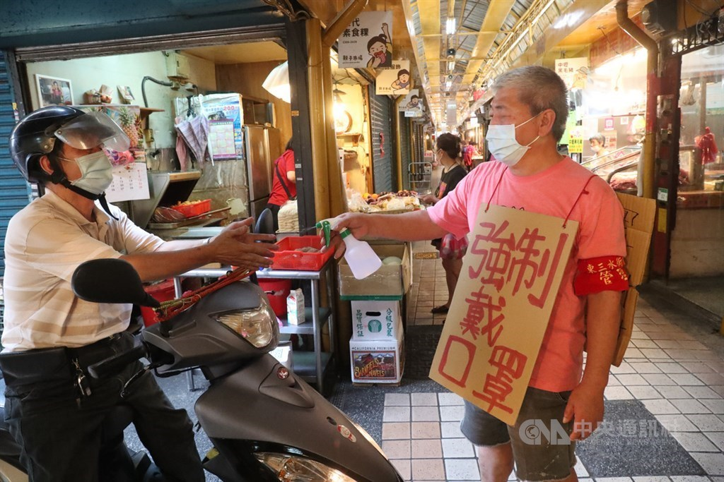 A man wears a sign reminding shoppers in a market in Taipei that wearing a face mask is mandatory. CNA photo May 15, 2021