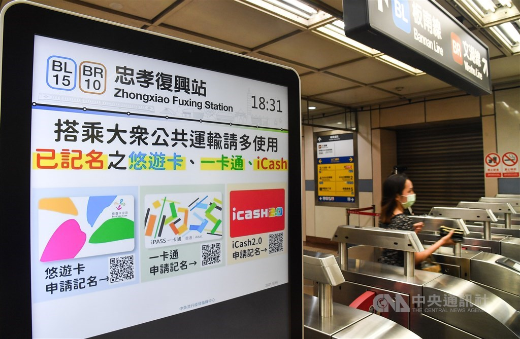 A screen displays a message that encourages people to register their electronic payment cards at Taipei Metro