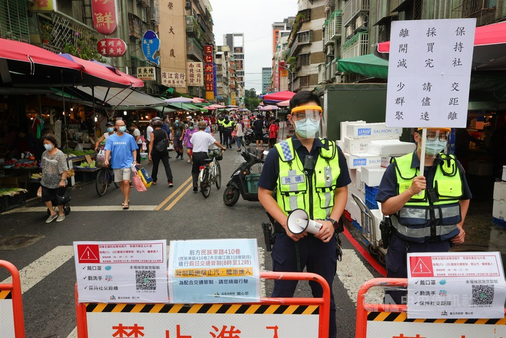 Policemen guard the entrance to a street market in Taipei and remind shoppers spend as little time in the market on Sunday. CNA photo June 6, 2021