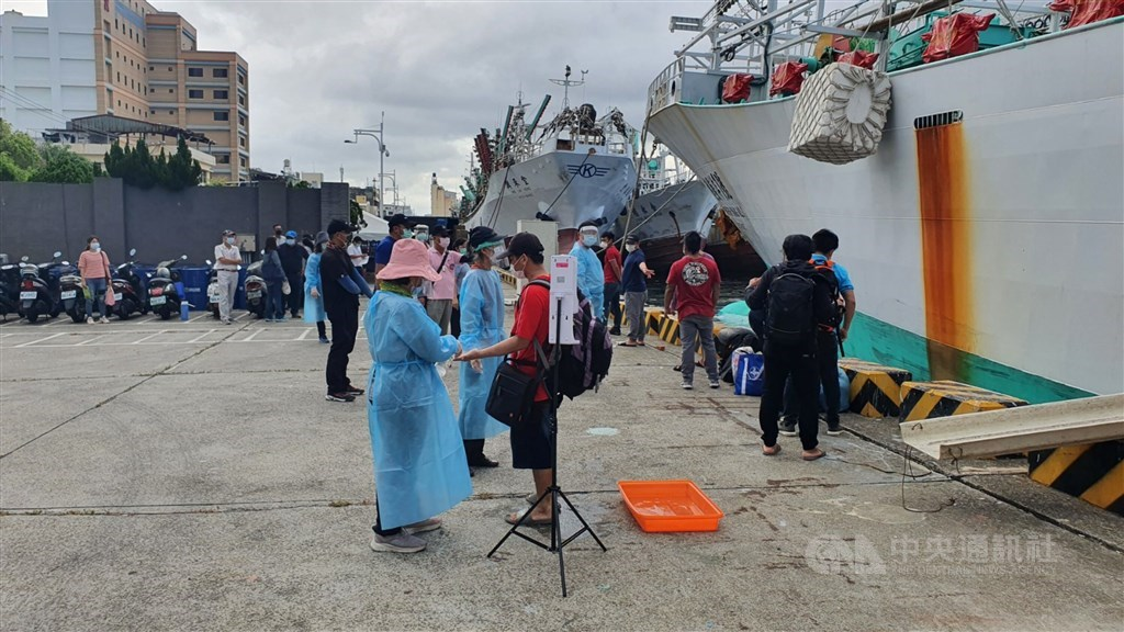 Fishermen are greeted by medical workers on arrival in Kaohsiung Tuesday. CNA photo June 15, 2021