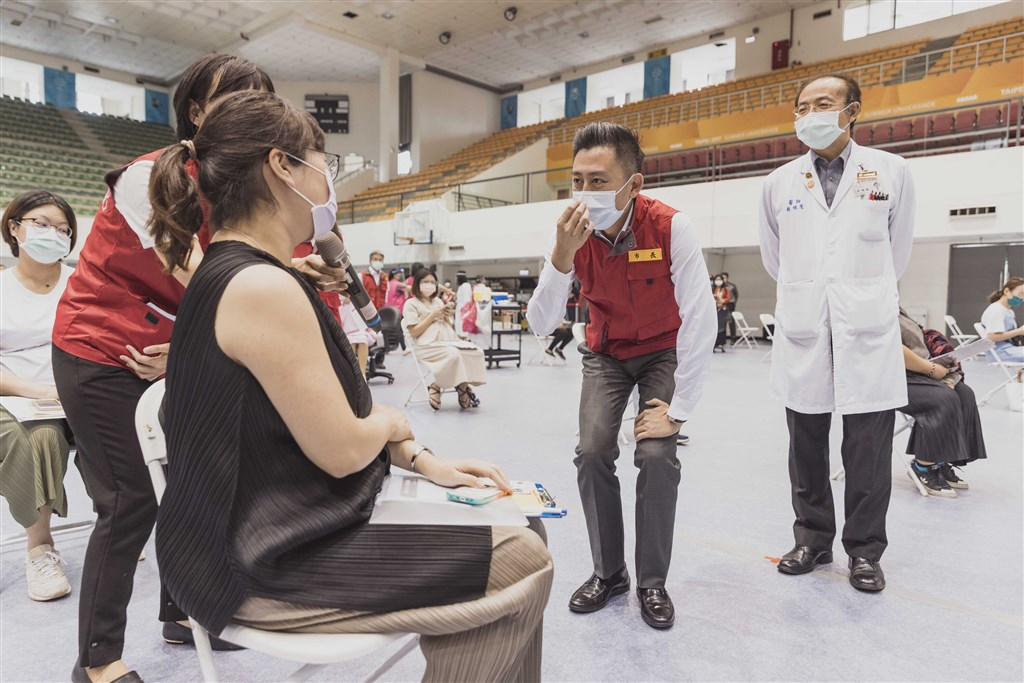 Hsinchu Mayor Lin Chih-chien (center) chats with a pregnant woman at a COVID-19 vaccination site in the city Tuesday. Photo courtesy of Hsinchu City government