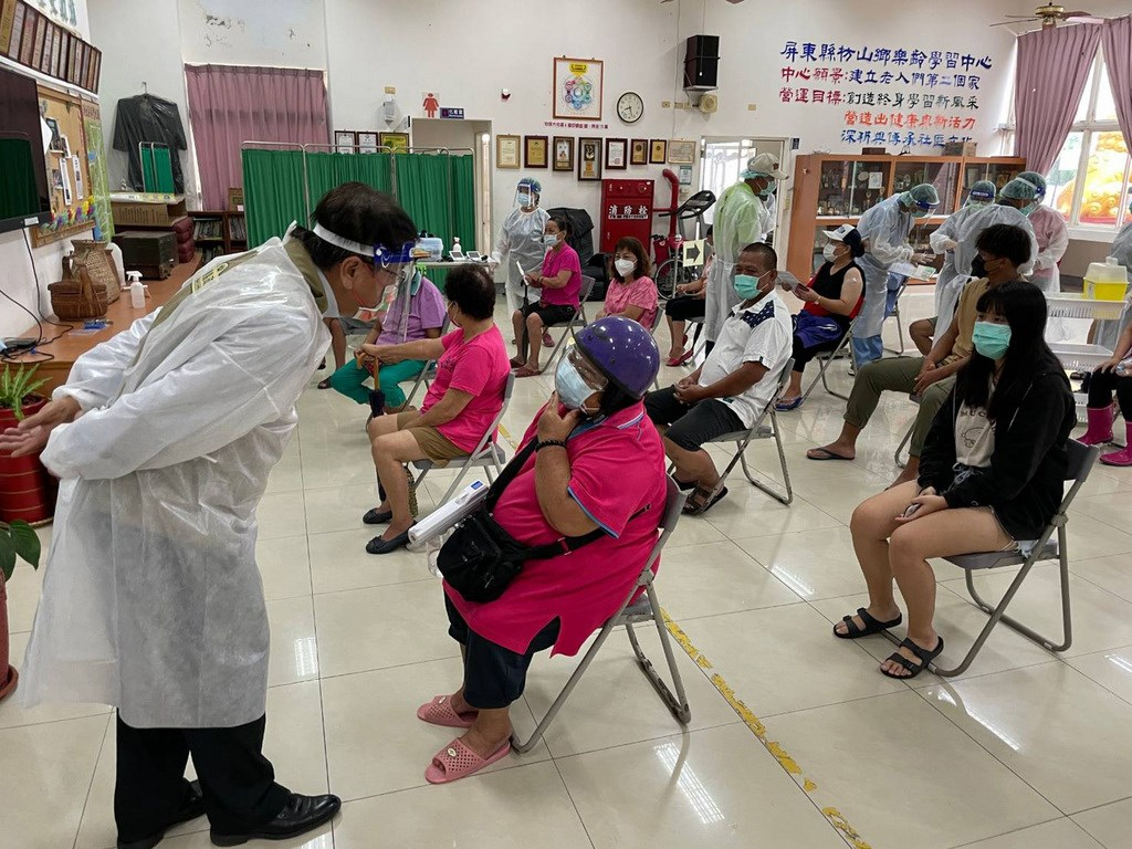 County Magistrate Pan Meng-an (left) chats with residents waiting to receive a dose of a COVID-19 vaccine on Sunday. Photo courtesy of Pingtung County government