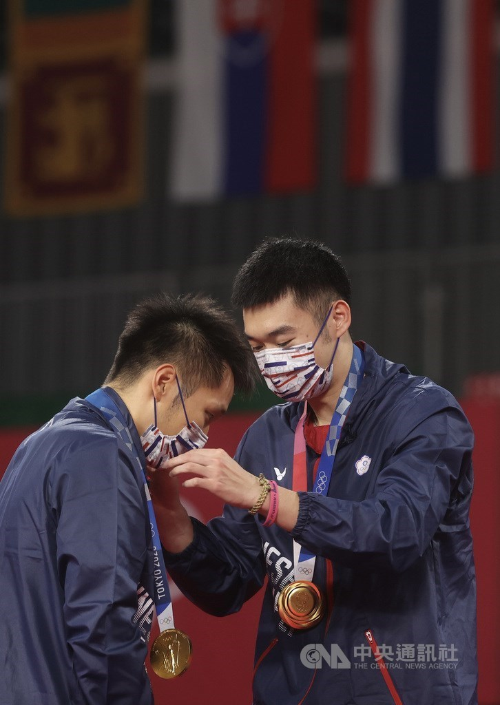 Want Chi-lin (right) puts the gold medal on Lee Yang. CNA photo July, 31, 2021