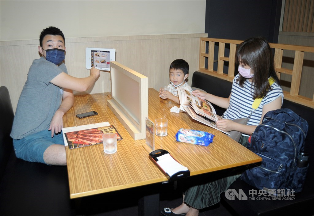 A family dines in a restaurant in Taoyuan, where a divider was set up in the middle of the table. CNA photo Aug. 21, 2021