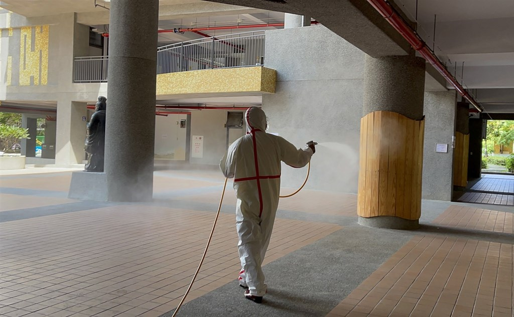 A New Taipei city worker sprays disinfectant in a school Tuesday amid growing number of COVID-19 cases among children. Photo courtesy of New Taipei City Department of Environmental Protection