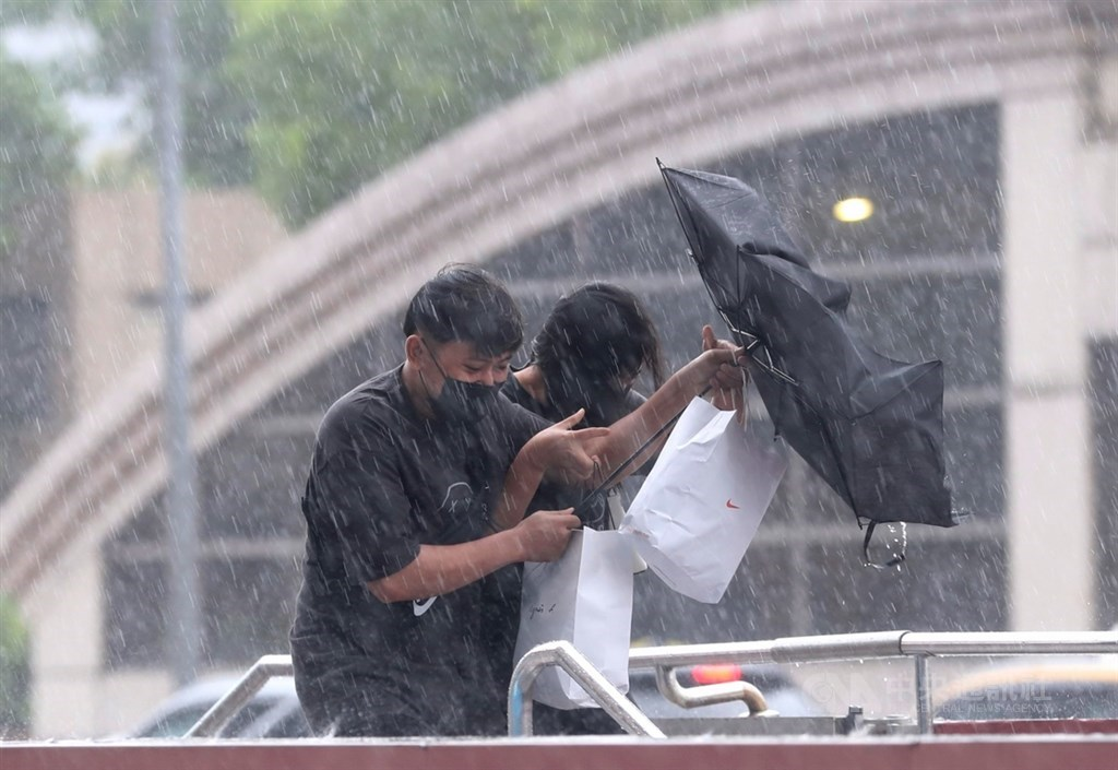 People caught in the rain in Taipei. CNA photo Sept. 12, 2021