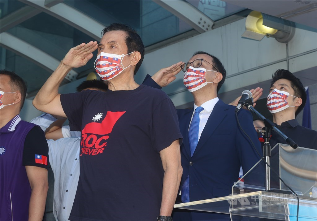Former President Ma Ying-jeou (front) and Kuomintang Chairman Eric Chu (behind Ma) salute when attending the opposition party