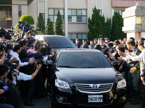 取材対象を乗せた車を囲む報道陣=資料写真