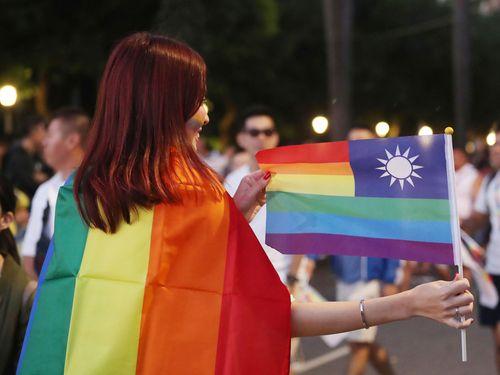 中華民国国旗をレインボーフラッグのようにアレンジした旗を手に持つLGBT(性的少数者)パレードの参加者=2018年10月27日台北で撮影