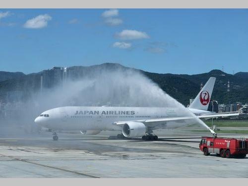台北松山空港で30日、放水アーチで送り出される羽田行きの日航機