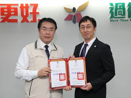 黄偉哲台南市長(左)から「城市外交顧問」の任命状を手渡される野崎孝男さん=同市提供