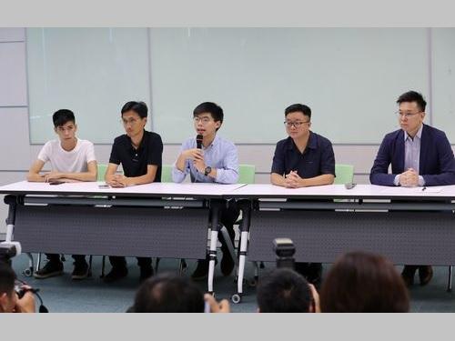 記者会見に臨む黄之鋒氏(中央)、朱凱廸氏(左から2人目)、民進党の林飛帆副秘書長(右端)ら