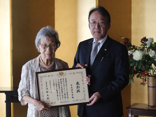 日本台湾交流協会台北事務所の沼田幹夫代表(右)から表彰状を受け取る台北俳句会の代表者